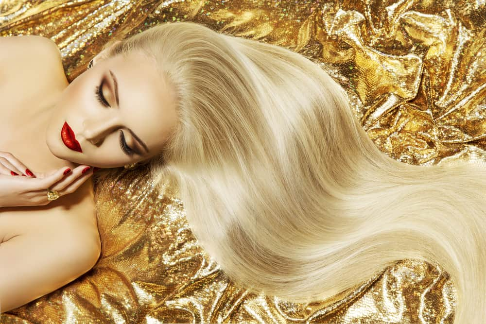 A model with long blond hair on a background of gold