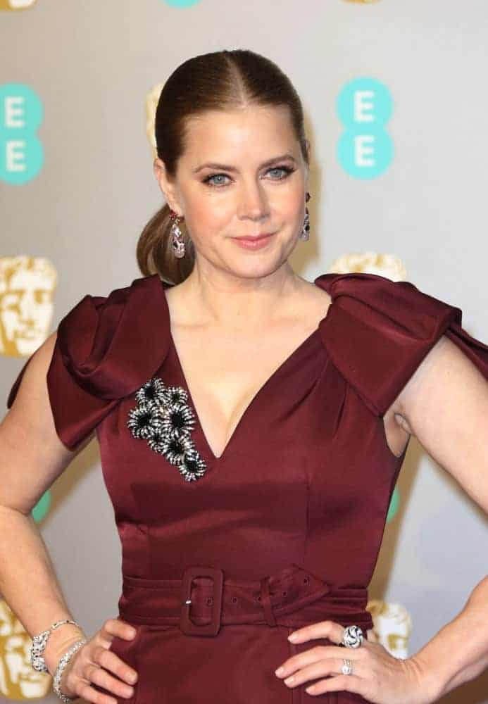 On February 10, 2019, Amy Adams attends the 72nd British Academy Film Awards at the Royal Albert Hall. She wore a maroon dress with a brooch to match her slicked-back auburn ponytail hairstyle.