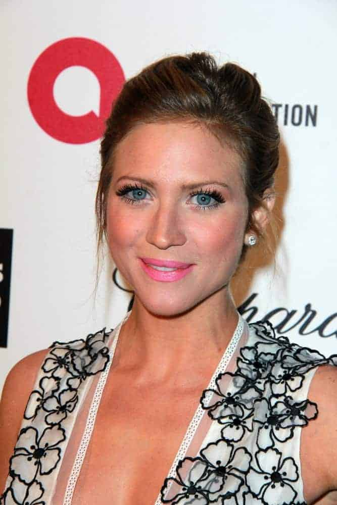 Brittany Snow was at the Elton John Oscar Party 2015 at the City Of West Hollywood Park on February 22, 2015 in West Hollywood, CA. She wore a sheer floral dress to go with her dark upstyle bun hairstyle with loose tendrils.
