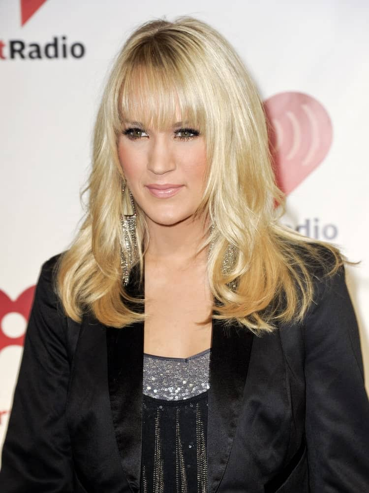 On September 23, 2011, Carrie Underwood appears on the red carpet at the 2011 iHeartRadio Music Festival wearing a black outfit and layered waves with full bangs.