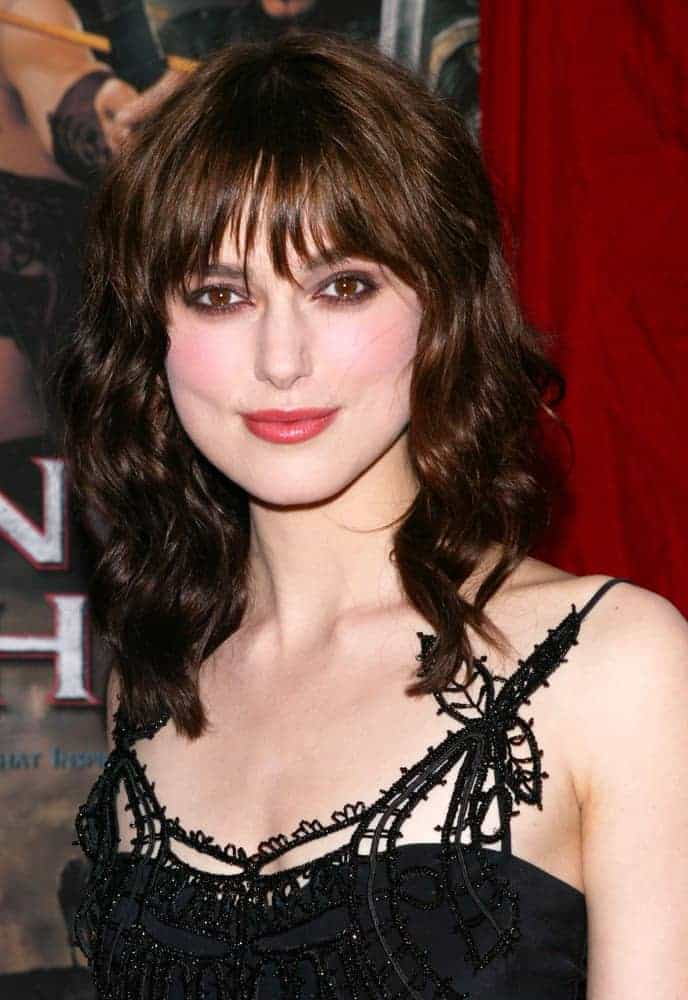 Actress Keira Knightley was at the world premiere of King Arthur at the Ziegfeld Theater on June 28th, 2004 in New York City. She wore a stunning black dress with her shoulder-length dark wavy hairstyle that has wispy layered bangs.