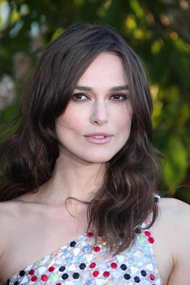 Keira Knightley attended the annual Serpentine Galley Summer Party at The Serpentine Gallery on July 1, 2014, in London, England. She came in a colorful dress to pair with her shoulder-length wavy, tousled and layered hairstyle.