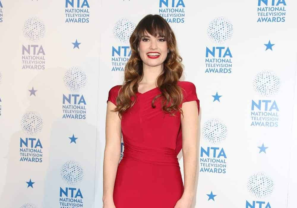 Lily James was in the winners' room at The National Television Awards (NTA's) 2013 held at the O2 arena, London on January 23, 2013. She wore a lovely red dress that pairs well with her red lips and long brunette hairstyle that has waves, layers, and long side-swept bangs.