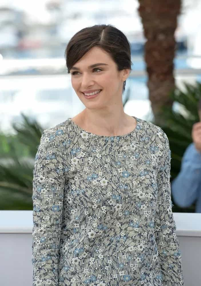Rachel Weisz flashes a smile in a floral-patterned long sleeve dress and pulled her brunette hair back into a chic bun as she attends the photocall for her movie
