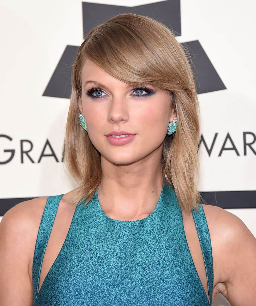 When it comes to different types of bangs, Taylor Swift knows how to rock them all. Here she looks stunning in bangs that have been gently swept to a side. Tucking her shoulder-length hair behind the ears allows the studded earrings to stand out and highlight her side-swept bangs all the more.
