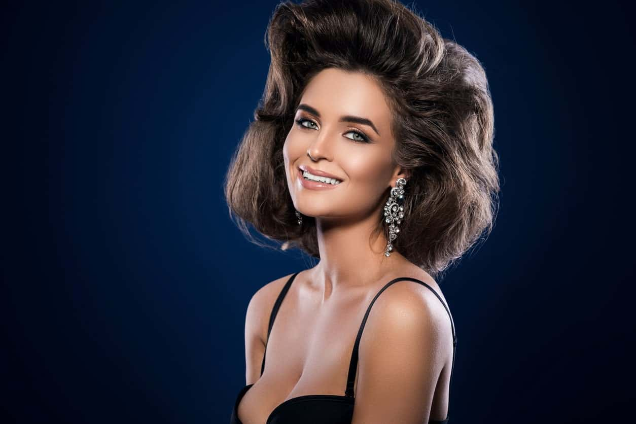 Wear your hair loose with a statement pompadour. Ask your stylist to take the thick hair in the front and curl and sweep it to the side. Giving a 1960's Hollywood look. The look works great for women with shoulder-length and thick hair.