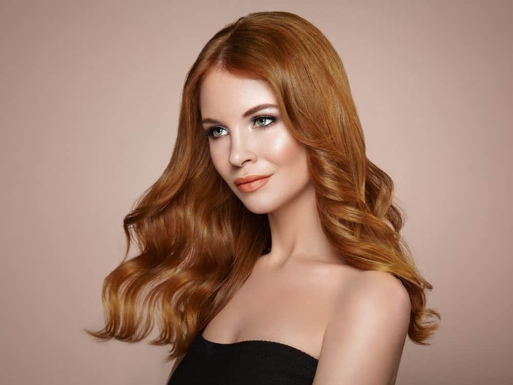 This is a classic, elegant haircut that will suit just about anyone. The shoulder-length soft curls standout in the auburn color.