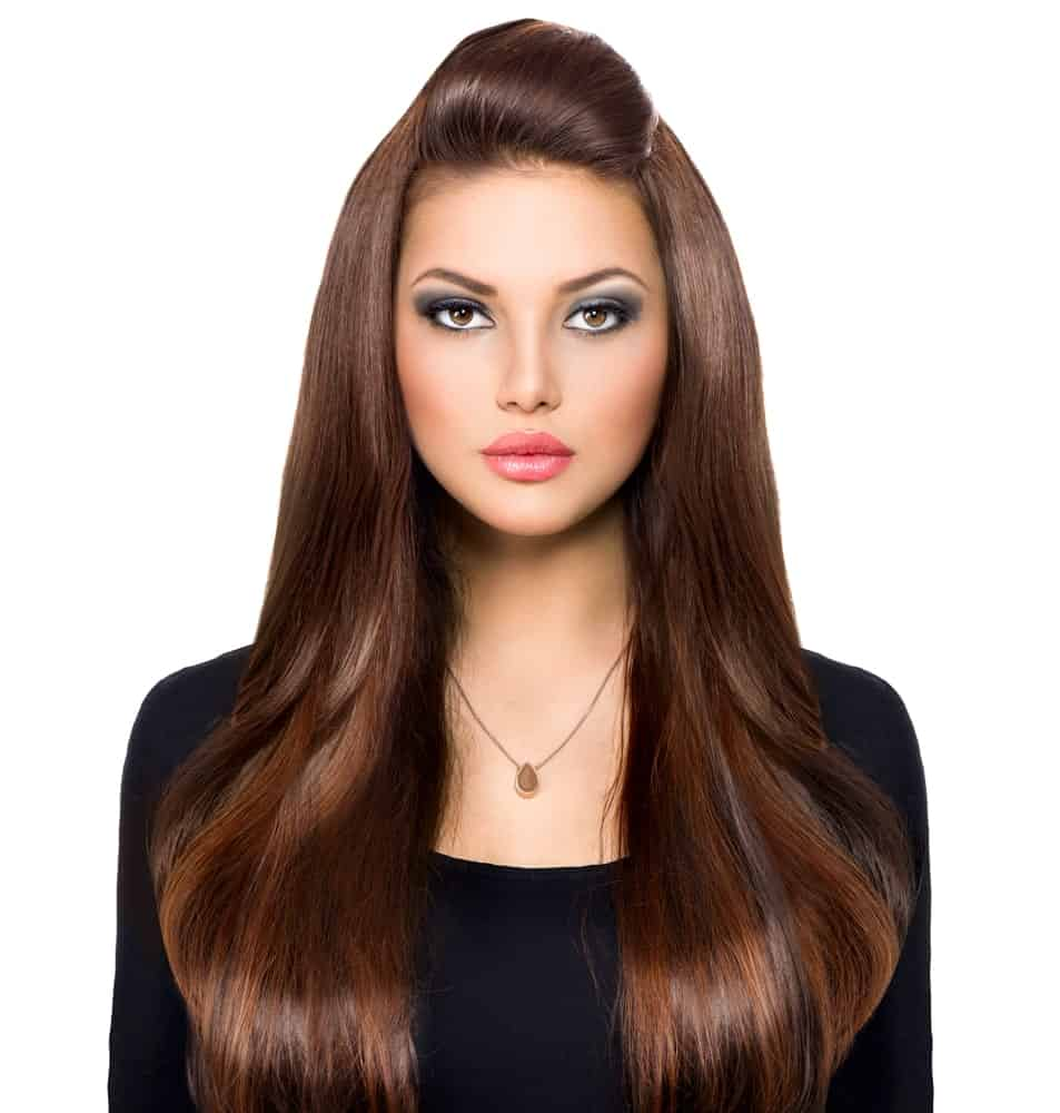 This is a classic example of a straight brunette hairstyle with healthy locks of hair flowing down on both sides and a poof in the front. This kind of style gives the hair great volume and structure.