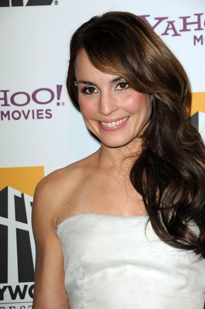 This hairstyle is the perfect example of long side bangs. Noomi Rapace looks absolutely stunning with her long hair sporting soft lose curls gathered at one side, with bangs completing the look.