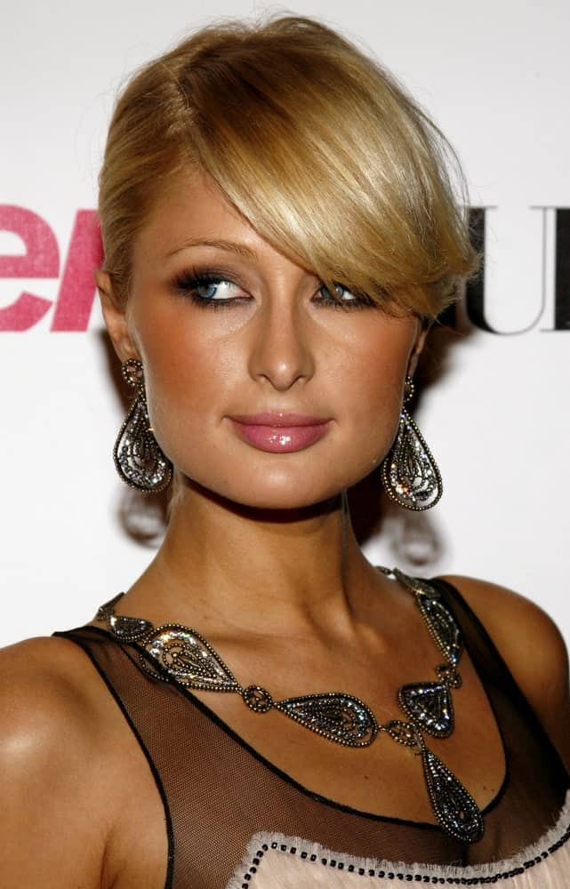 The long side bang is swept to one side with the rest of the hair in a tightly clipped bone. The bangs are straight and sleek, adding attention to the cheekbones.
