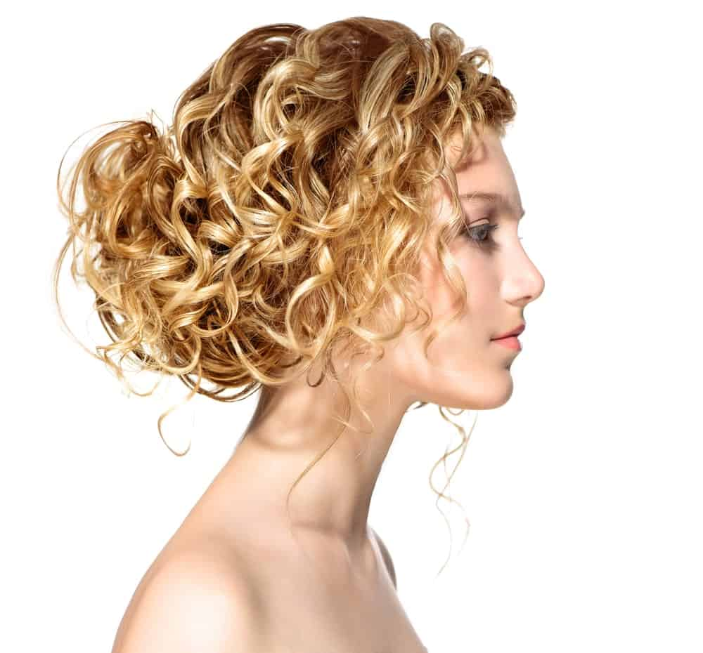 This hairstyle is the perfect messy look that will leave you looking chic and trendy. The hairstyle features a low hanging messy bun at the back of the head coupled with loose strands of hair falling around the face. It is the ideal hairstyle for all the busy bees out there who cannot spare more than a few minutes for styling up their gorgeous long and blonde curly hair. To recreate this look make sure that your bun is loosely tied, putting the power of your curls to full use.