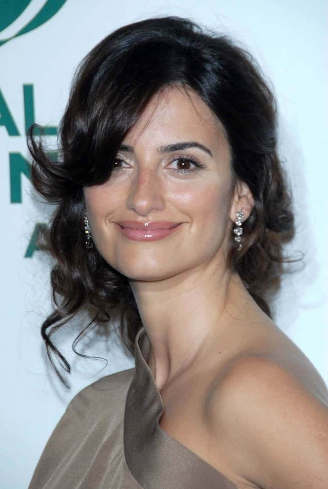 Check out this amazing look sported by the ever-lovely, Penelope Cruz. The hairstyle features long brunette hair tied in a loose, messy side bun. Coupled with side bangs, this fair style gives you the perfect opportunity to show off your earrings. If you are looking for a contemporary hairstyle that portrays class, elegance, and distinctive beauty, all in one— this is the hairstyle for you!