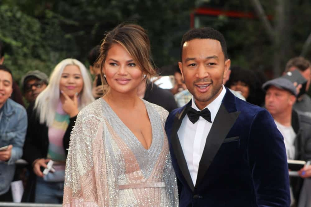 Chrissy Teigen has her hair up in a messy bun with a straight side bang to frame her face perfectly. The soft honey tones in her brown hair look absolutely gorgeous.