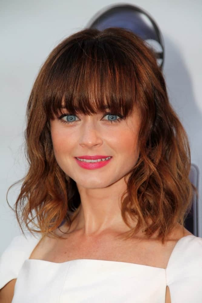 Would you fancy a fiery, slightly disheveled look? If you like to stand out from the crowd, check out this amazing hairstyle modeled by Alexis Bledel. It features blunt bangs and short hair with distinct curls. This hairstyle is perfect to draw attention to your eyes and lips without looking bland or flat.