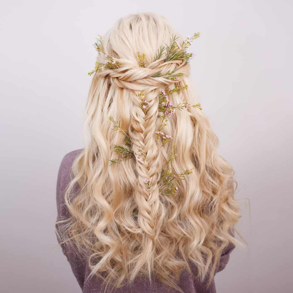 "Bring out your inner ""Khaleesi"" with this ultra-awesome hairstyle for long curly blonde hair. If you are a fan of braids, you will love this hairstyle that features two styles of hair braids, one forming a crown at the back of the head while the other, which is a fishtail, adding texture to the hair and giving it a gorgeous look. To finish off the look, add a floral touch by decorating your hair with flowers. Whether you use fresh flowers or opt for the artificial ones that are specially designed for hair – it is a great way to take your hairstyle to the next level and add an X-factor to it!"