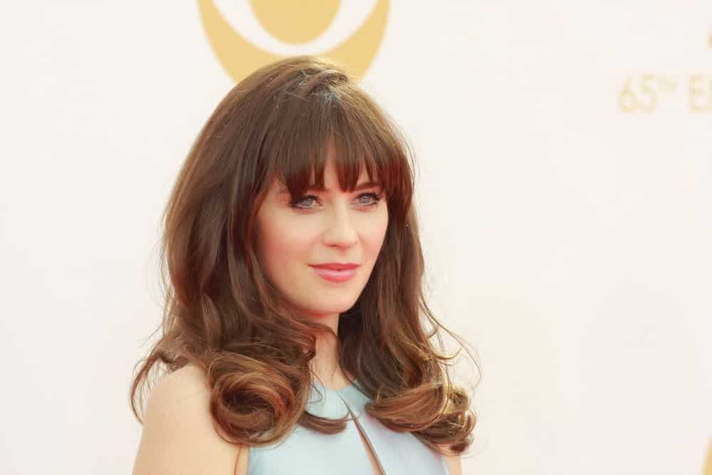 Zooey Deschanel is a true advocate of bangs. The hairstyle features bangs with medium-length hair that slightly curve toward the ends. This hairstyle perfectly frames the face and adds a soft touch to the overall look.