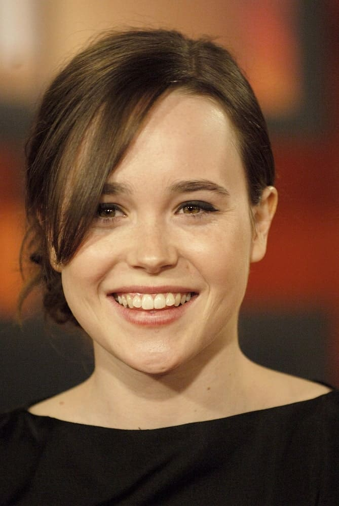 Ellen Page is supporting a side bun complimented by the side long bang. The soft brown color looks wonderful and brings out the warmth of her brown eyes.