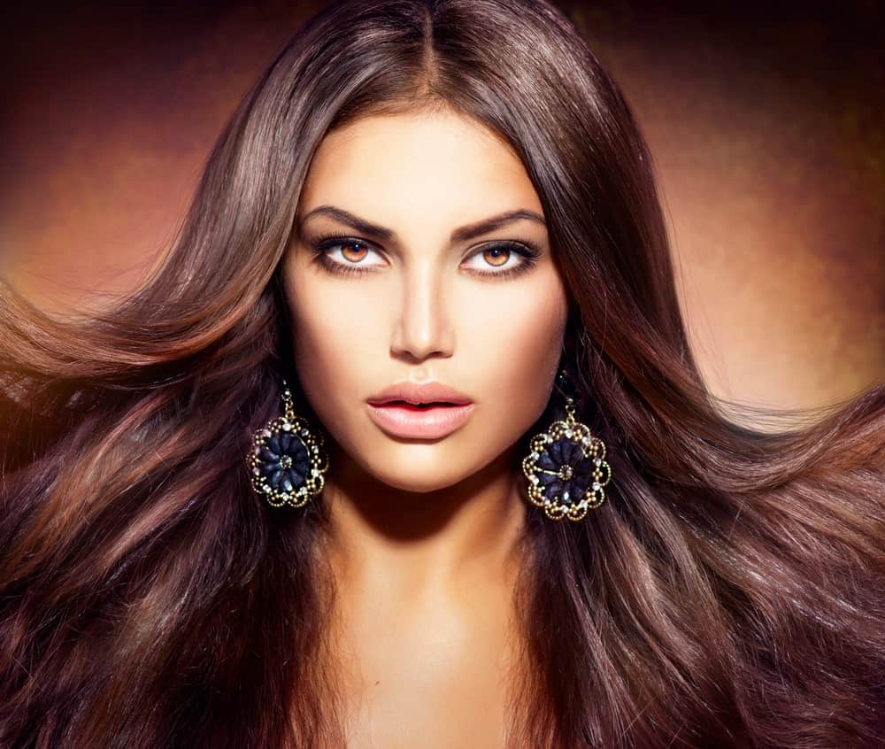 This is a truly dazzling and dramatic-looking hairstyle with a simple middle parting, but with one exception. The hair seems to have been styled in a way that it doesn't stick flat to the face but is super bouncy, voluminous and appear to flow in an outward direction.