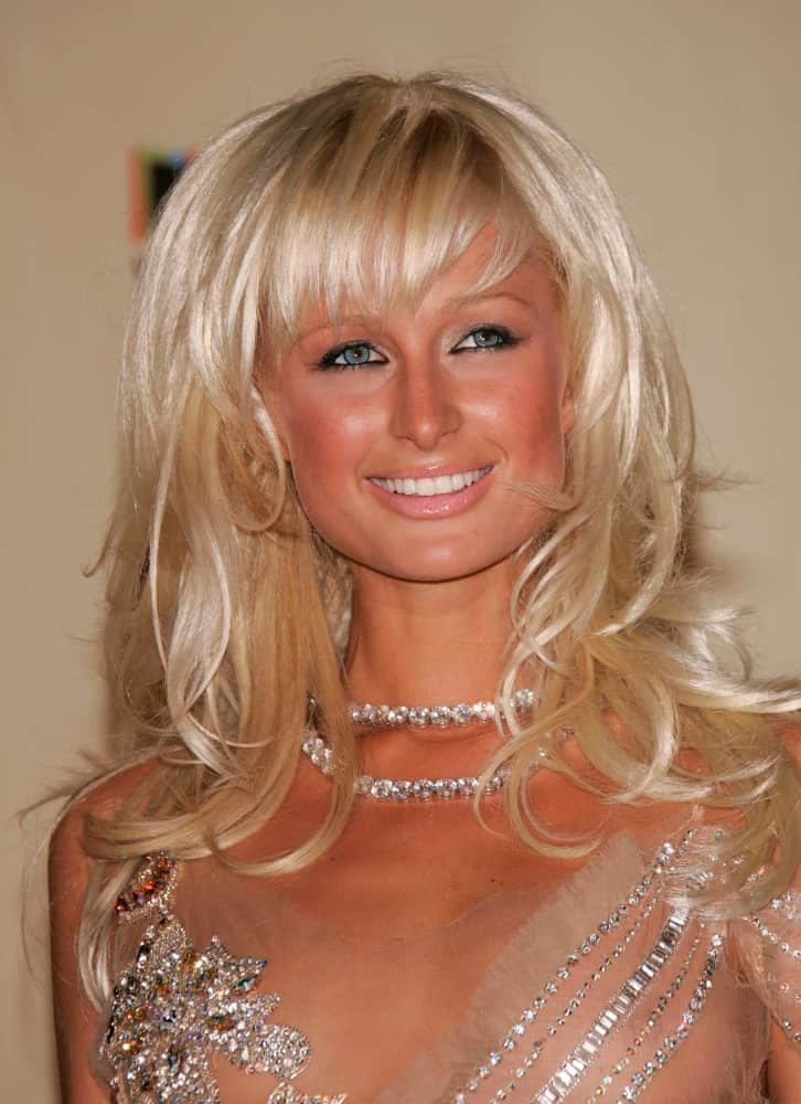 Paris Hilton was one of the first celebrities to make the combination of short bangs and wavy hair a trend. The wavy hair frames her face perfectly while the bangs highlight the smoky makeup of her eyes. The hairstyle also makes her forehead seem smaller.