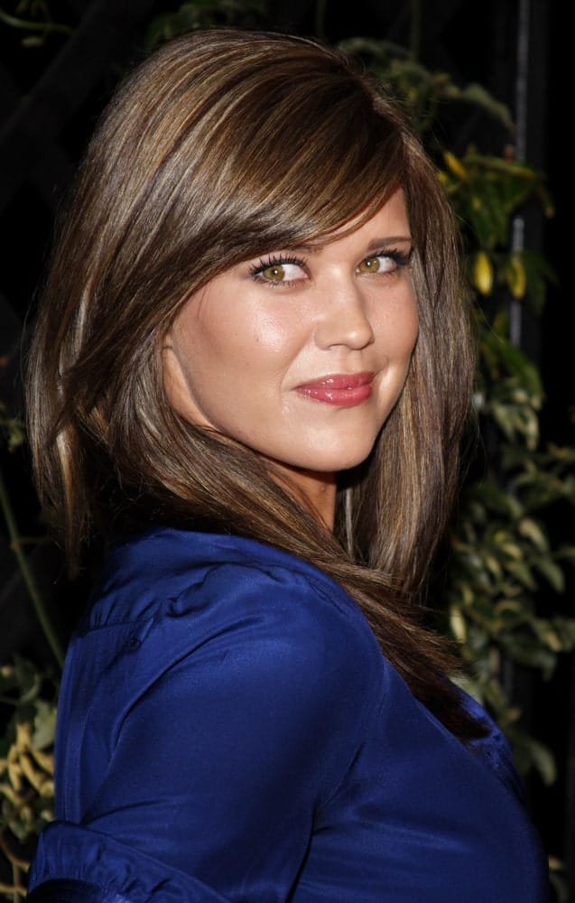 This one is a classic! Sarah Lancaster dawns a beautiful look with straight medium-length hair and full side bangs. Resulting in an absolutely lovely look, the voluminous hair frames her face perfectly.