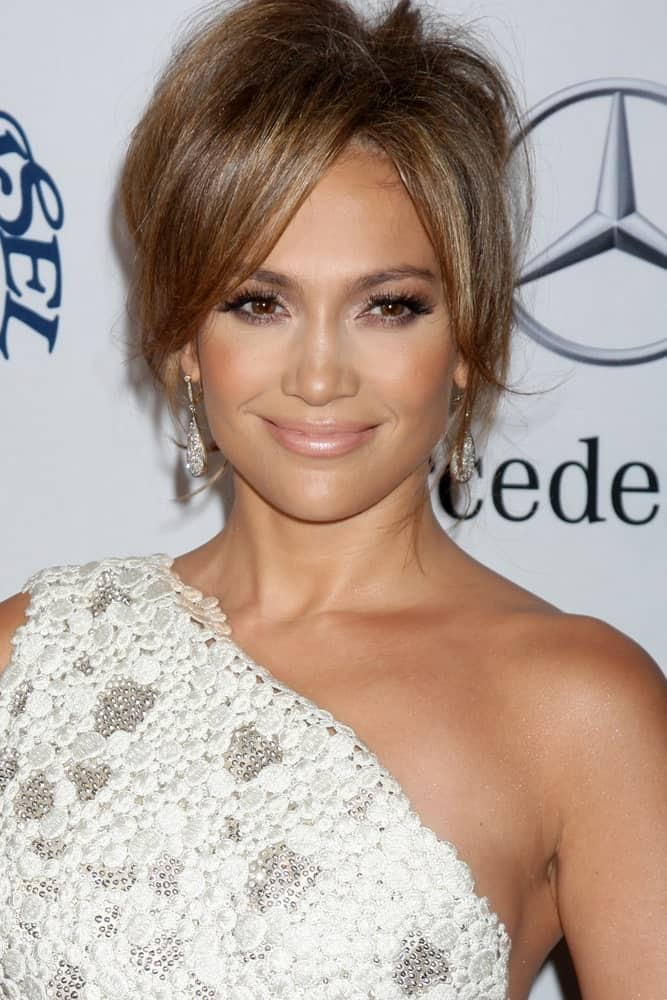 The long side bangs frame Jennifer Lopez's face perfectly and ends at her cheekbones. They are paired with a puffy hairdo and bun that looks messy and unruly.