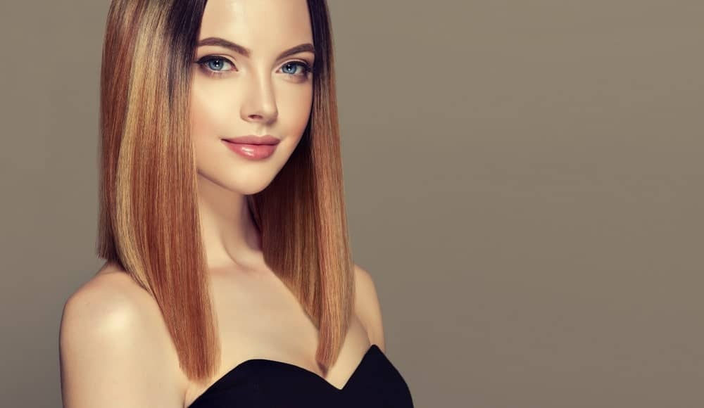 This angled lob has so many colors, it looks like there is a full palette of red, brown and blonde dyes in there. This beautiful woman is rocking an ultra-modern lob that skims her shoulder at the back but is angled and cut much longer in the front. This style is super attractive and super sophisticated.