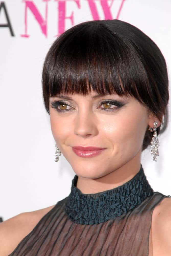 Here's another hairstyle that you can sport without having to worry about swiping away loose strands of hair out of your face. Modeled by Christina Ricci, this hairstyle features blunt bangs. The rest of the hair is tied in an elegant low-bun at the back. If you are planning to complete your look with earrings, this hairstyle may be the right choice for you!