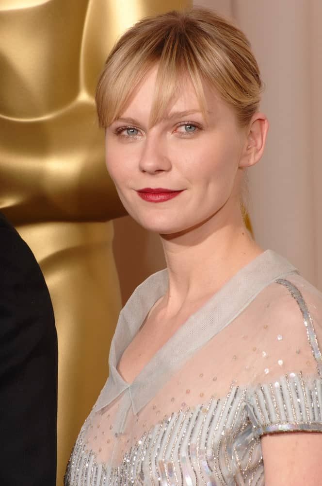 Kirsten Dunst is supporting fringes with a cute ponytail at this Academy Awards event. The hairstyle makes her look like the friendly girl next door. It accentuates the jaw line while also giving her a youthful look overall.