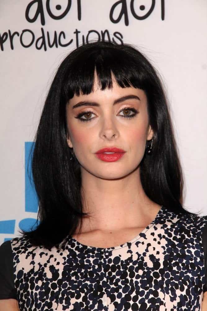 You just can't go wrong with shiny shoulder-length sleek hair with short cropped front bangs. Modeled by Krysten Ritter, the hairstyle features short bangs that cover only half of the forehead, giving you the liberty to showcase your eyes and eyebrows. To amp things up, the sleek look adds a chic modern touch