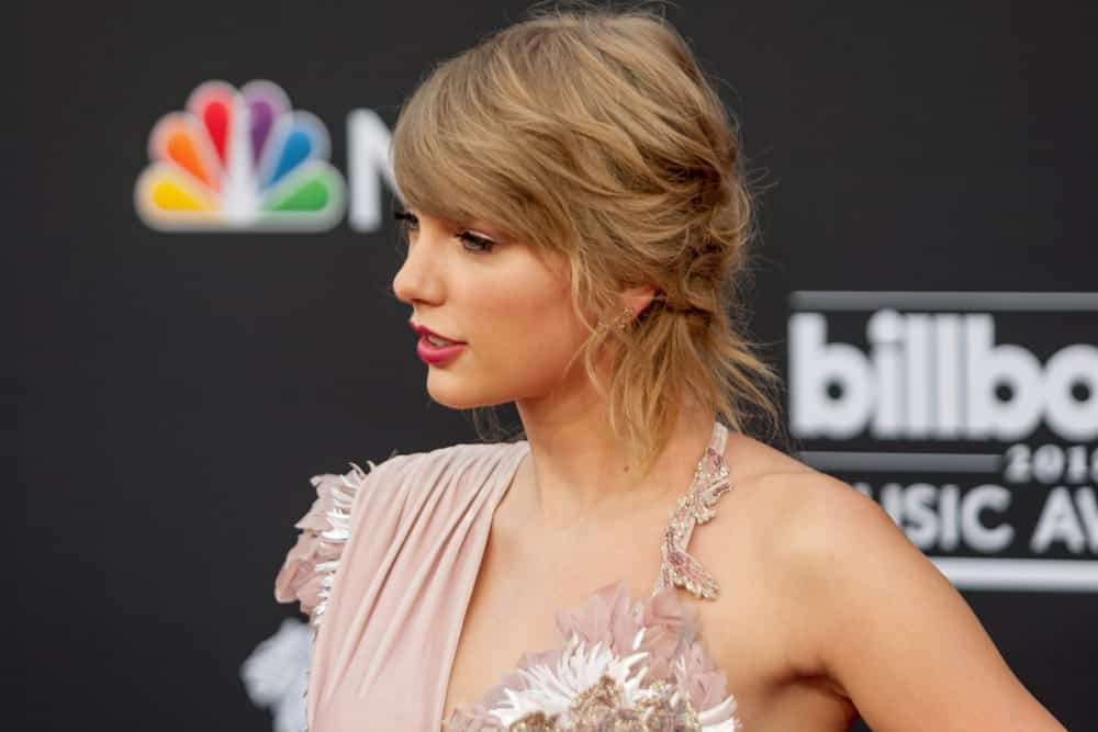 Some strands of Taylor Swift's long side bangs have been pinned to the side but some strands still flow freely. The rest of the hair is in a messy cut and looks stunning.