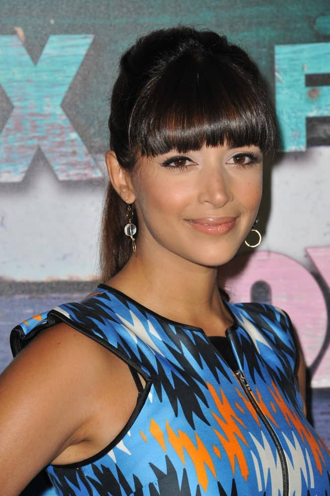 Hannah Simone proved that blunt bangs can go with almost any hairstyle. If you are a fan of blunt bangs, the good old ponytail is enough to create a dazzling hairstyle. It also gives you a chance to show off of your earrings!