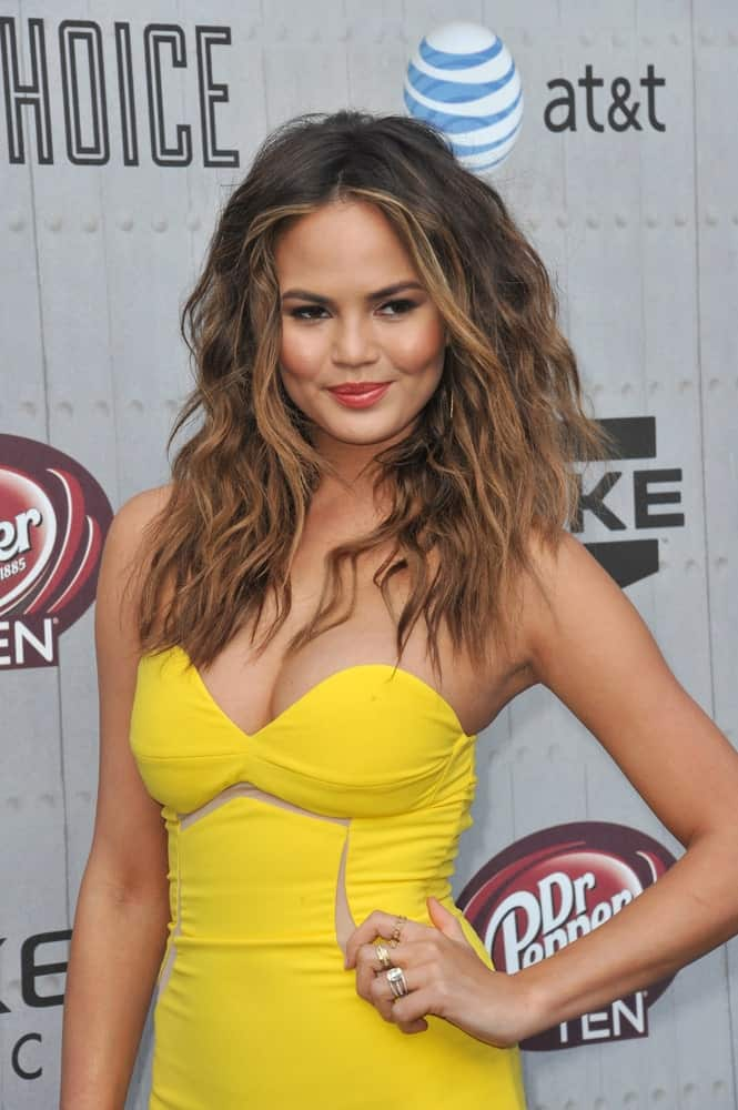 Want to make your hair more defined and volumizing? Chrissy Teigen shows you how. The model-turned-cookbook writer started with dark roots, which gently transitioned to toffee brown shades. She also added bright blonde highlights to the front of her locks. To give it more dimension, Teigen has added crimps to her long, flowing locks.