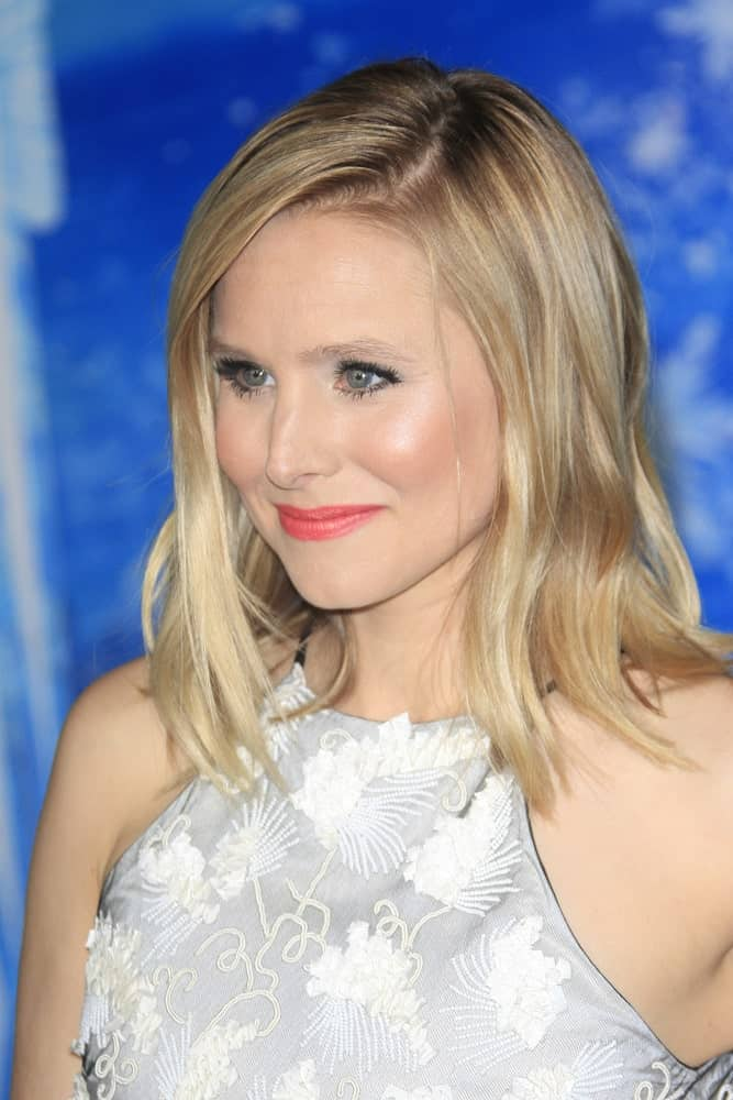 This is Kristen Bell with her shirt blond layers that sport a sleek, straight look and have been parted to the side.