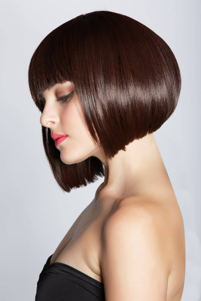 This is a classic, funky brunette angled bob with thick fringe-bangs in the front. The hair is super voluminous from the back and appears to be a little poofed up, giving the hair a very modern, trendy touch.