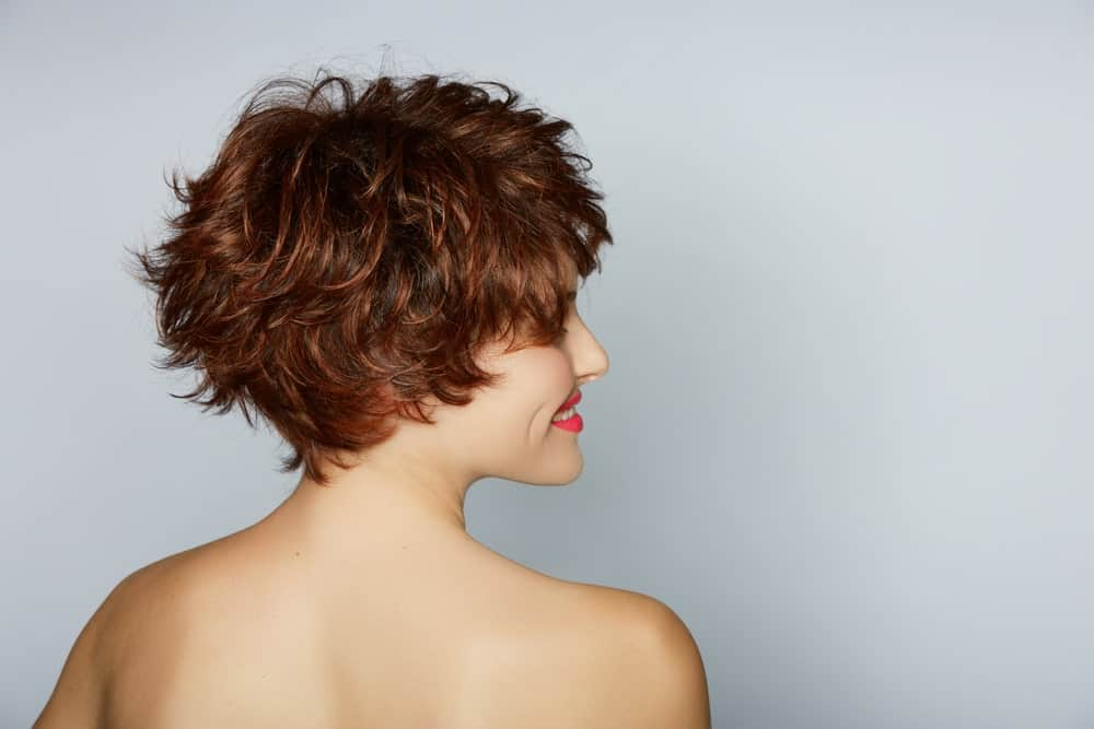 A classic side bun with curls and soft, sleek side bangs framing the face make for a great hairdo for any formal event.