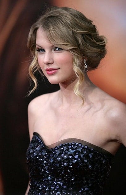 The tightly curled bangs frame Taylor Swift's face perfectly. They divert the attention to her eyes and will do the same for you. The rest of the hair looks heavenly since it is pinned perfectly into a messy bun.