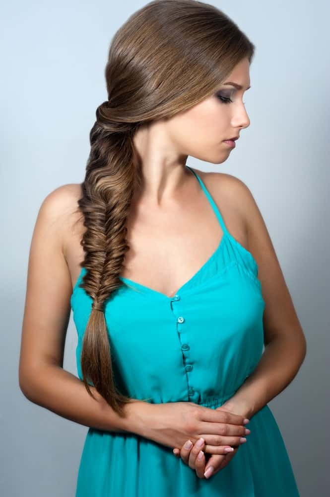With this cute hairstyle, you can create the perfect girl-next-door look. A lot of women believe that it is hard to style long straight hair without a stylish haircut. This hairstyle is here to bust this myth. Lovely for long brunette hair, the hairstyle features a fishtail braid. Around the neck, the silky brunette hair is simply twirled and twisted to one side before braiding it into a stylish-looking fishtail braid.