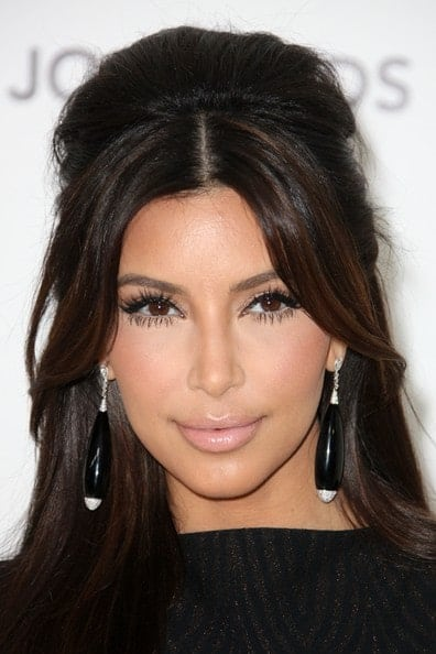 Here, Kim Kardashian has parted her bangs through the middle and swept them elegantly to the side. The rest of the hair is in free wavy curls while on top some backcombing has been done for a puffed up look. This is a great look for longer, slim faces.
