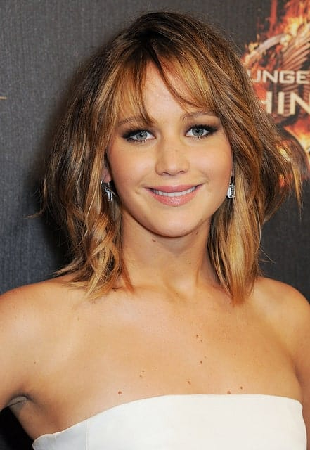 Whether she is sporting long or short hair, Jennifer Lawrence's thick tresses are designed to transform into a huge variety of looks. Here, the actress has her hair styled in piece-y bangs that give way to jagged, tousled layers. The actress has added some strawberry-blonde highlights to give her hair even more definition.
