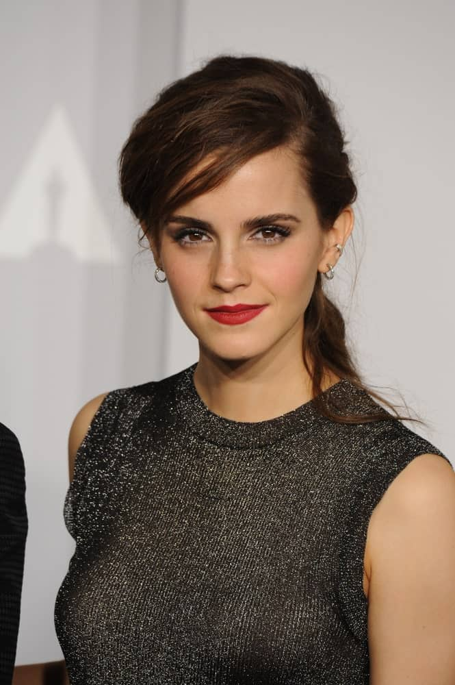 Emma Watson has swept her bangs to the side in a messy way. This pairs well with her perfect earrings, red lips, and fierce eye makeup perfectly. The rest of her hair is tied back in an untidy pony, which actually compliments her outfit and makeup in the best way possible. This look will definitely make you look effortless as well.