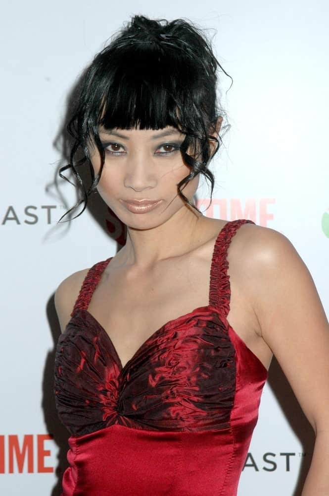 This is not your ordinary blunt bangs and hair down kind of hairstyle. Modeled by Bai Ling, it features straight-cut blunt bangs covering the forehead. A few locks of tight curly hair hang loosely around on both sides of the face; help frame it to bring focus to the eyes. Finally, the rest of the hair is tied in a bun at the back. End result – a perfect look!