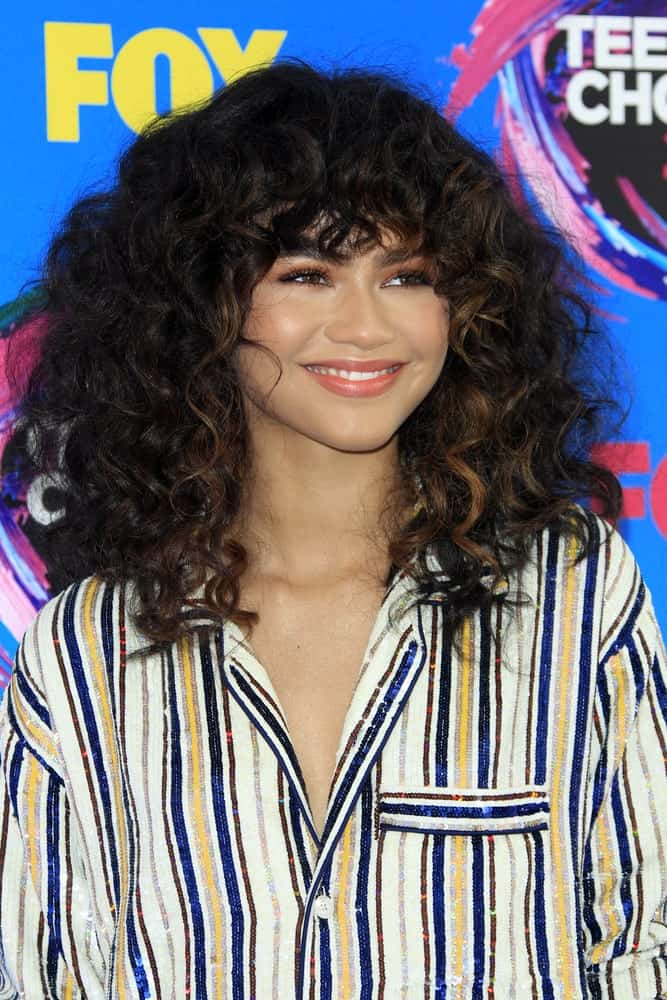 Bangs aren't just for straight hair! They look absolutely cute and beautiful on curly hair as Zendaya is proving here. They frame her face perfectly, making her look youthful and fun. They create a look which accentuates the jaw line and brings out the sparkle in her eyes.
