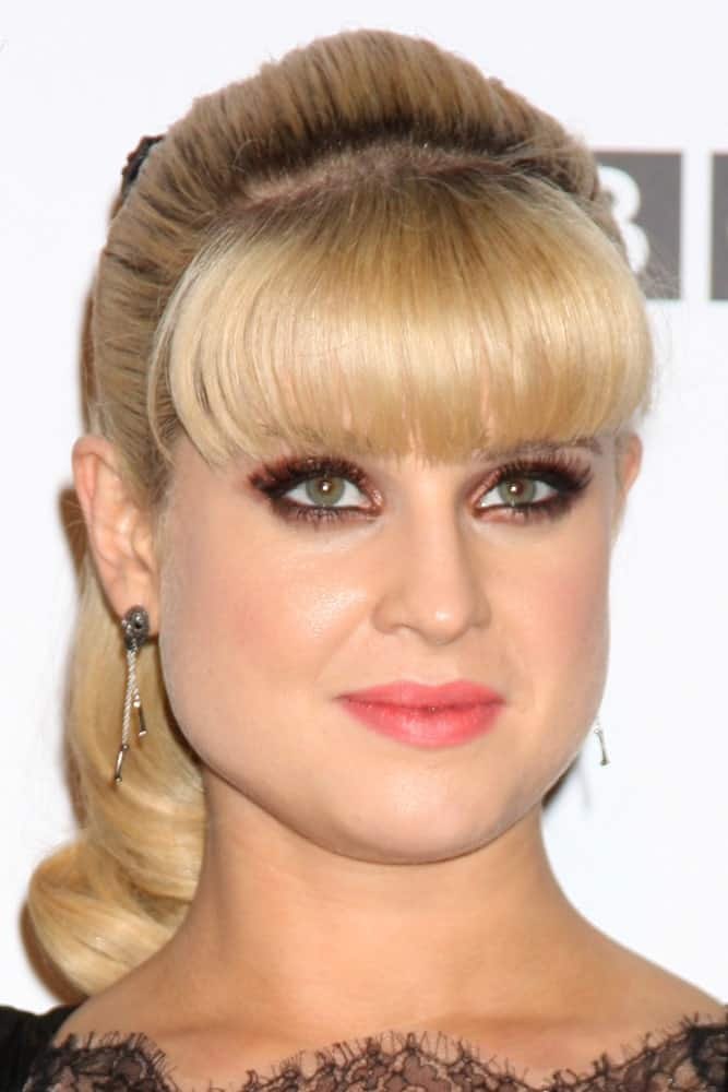 For the perfect evening look, recreate this hairstyle modeled by Kelly Osbourne. While blunt bangs are clearly the hero when it comes to this hairstyle, the rest of the hair is tied in a ponytail. Take notice of the volume of the hair. This makes sure that your hair does not look bland or too flat. To add the final touch, slightly curl the end of the ponytail.