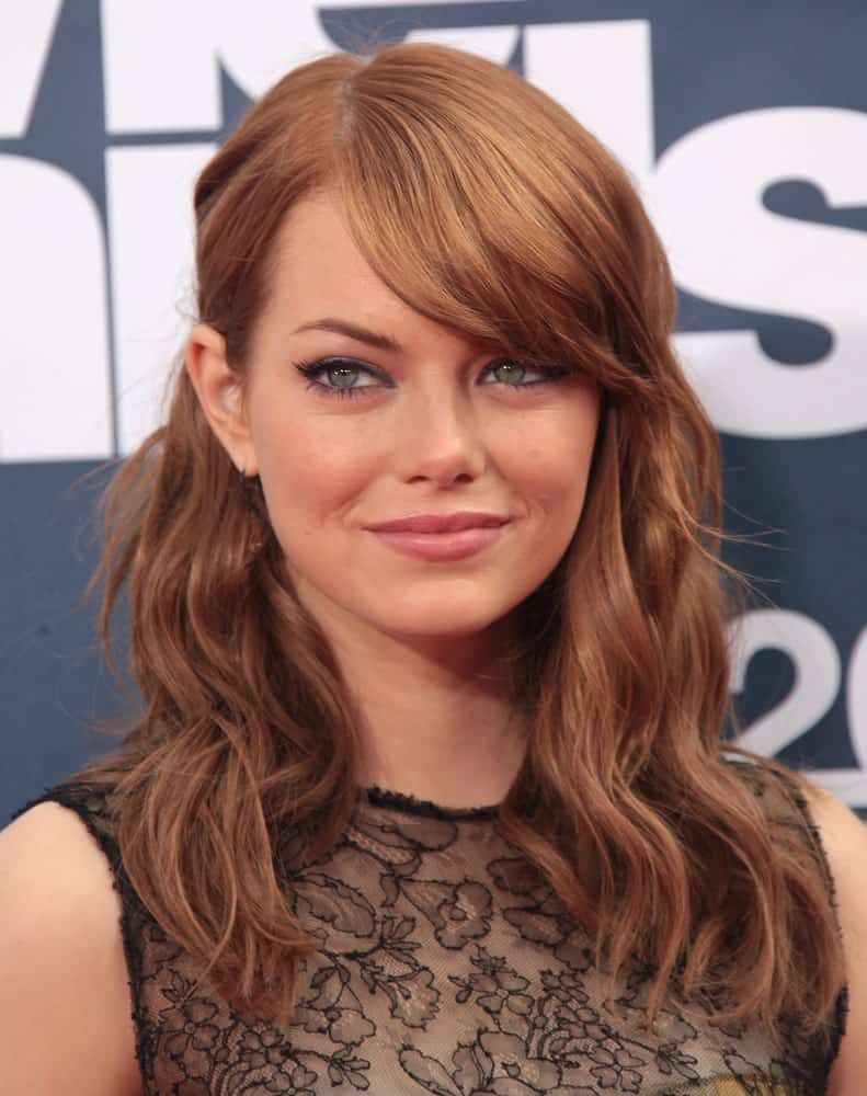 Emma Stone has been an advocate of side-swept bangs for a very long time. Take a look at how she looks stunning on the red carpet with her thick side bangs and the oh-so-amazing hazelnut hair color.