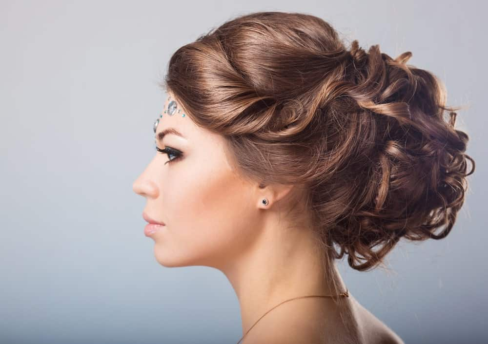 Feeling a little fancy? Go for this stylish braided bun style. The hairstyle features long brunette hair tied in a messy bun at the back of the head. In the front, the hair is tucked to the side. The same strands eventually end up in the bun. If you want to show off your earrings, this hairstyle is probably what you are looking for.