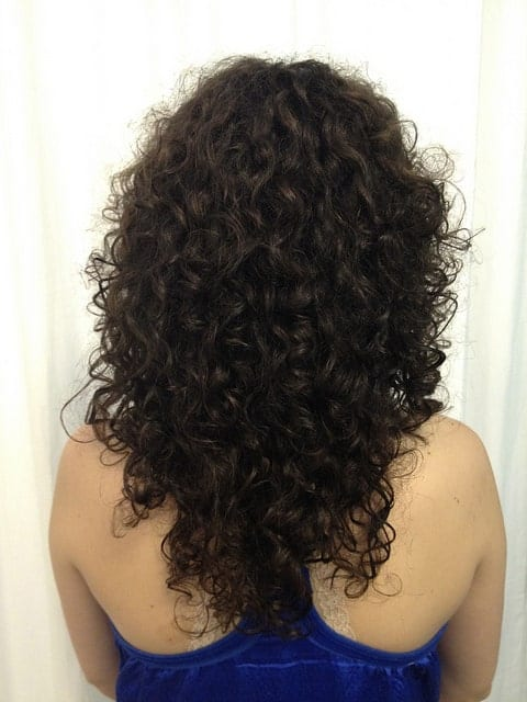 This is a more compact-looking curly hairstyle with small tight curls that are clumped together.