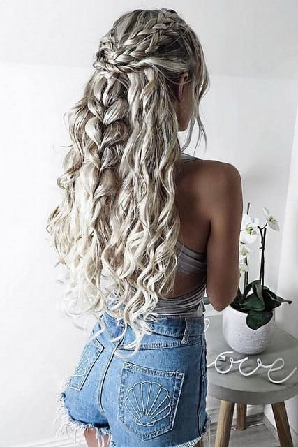 "Emilia Clarke sports a headful of long, platinum, braided locks in ""Game of Thrones."" Duplicate this look by asking your stylist to put some of your hair in varying styles of braids, while letting the rest of your hair flow down in loose curls."
