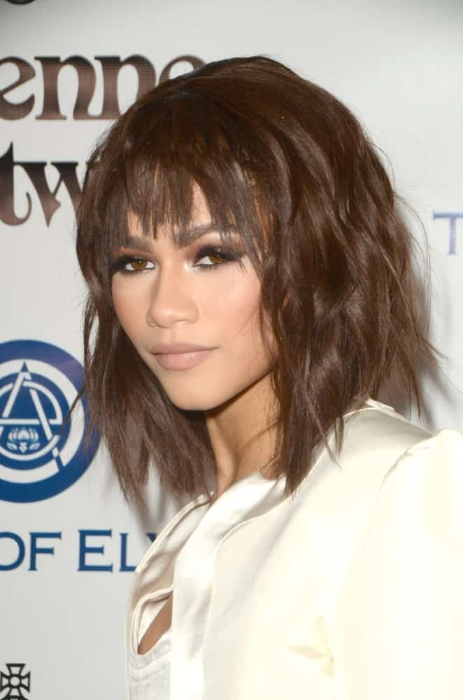 Sleek straight bangs have always been popular since they create a powerful, intense look. The brown straight bangs on Zendaya attract attention. They bring out the soft brown color of her eyes and gives life to the smoky makeup she has on.