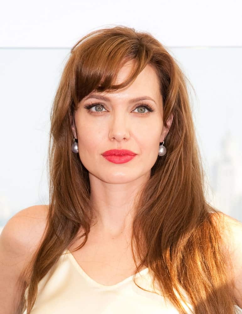 Angelina Jolie slightly sweeps her bangs to the side with free-flowing hair. The hues of chestnut brown straight hair make her look effortlessly elegant.