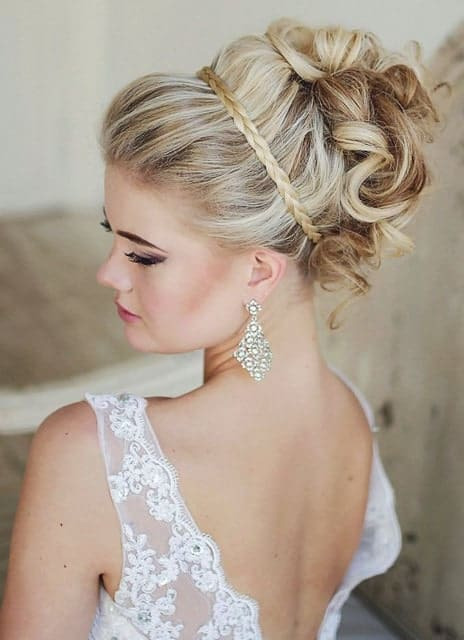 If you are going to a wedding, a great way to keep your thick hair off your face and neck is to style it up in an elaborate updo. Here, the model is sporting an updo with a braided headband and her thick curls pinned up in a classy updo.